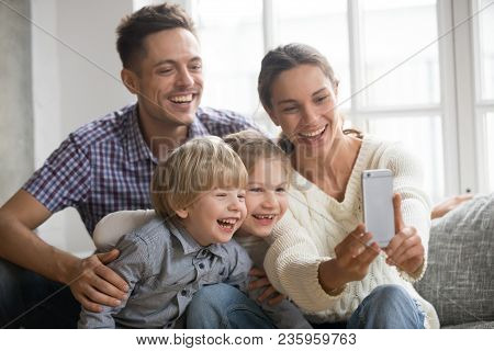 Cheerful Family With Children Laughing Taking Selfie Together On Phone, Young Mom Holding Smartphone