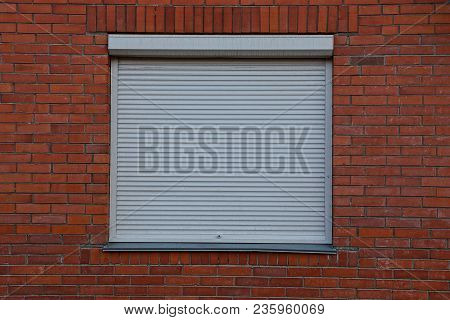 The Square Window Closed By Gray Jalousie On A Brick Wall