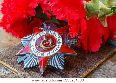 Soviet Order Of Patriotic War (inscription Patriotic War) With Red Carnations On An Old Wooden Table