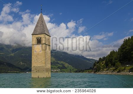 Flooded Church Tower In The Resia  Lake, Italy, Curon Against The Majestic Background Of The Wild La