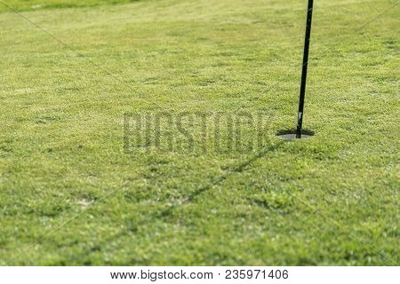 Putting Green On A Sunny Day With Hole And Flagpole
