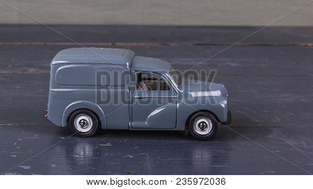 3d Metal Model Of English Car Gray Color On The Old Wooden Damaged Background, Close-up