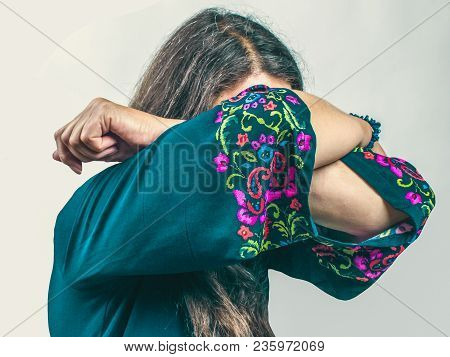 Sad Emotional Senior Woman With Long Gray Hair In A Turquoise Dress With A Pattern Standing With Clo