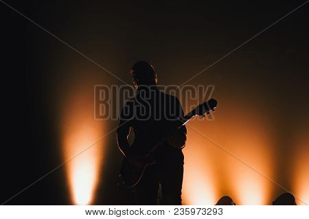Rock Band Performs On Stage. Guitarist Plays Solo. Silhouette Of Guitar Player In Action On Stage In