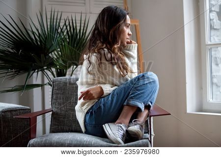 Sad Thoughtful Teen Girl Sits On Chair Feels Depressed, Offended Or Lonely, Upset Young Woman Suffer
