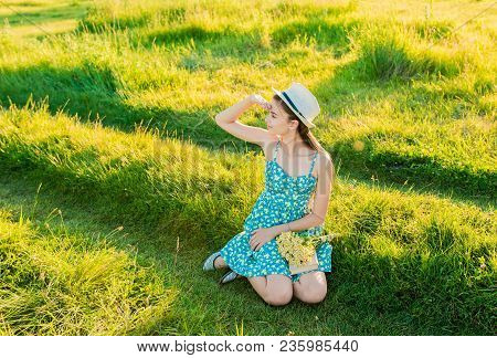 Young Romantic Girl Reading A Book Sitting On The Grass