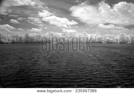 Vast Open Lake Surrounded By Trees In Summer In Infrared In Black And White, Conceptual