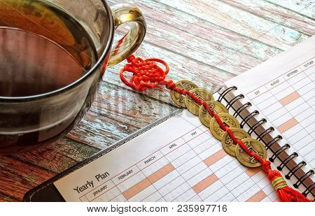 Traditional Chinese Coins On A Red Lace, A Notebook, A Cup Tea On A Wooden Table. Top View. Indoors.