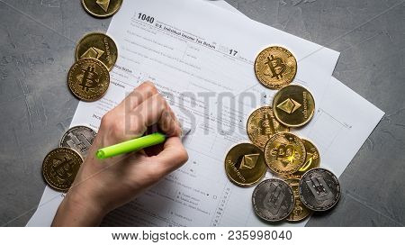 The Girl's Hand Fills The Tax Form For Paying Taxes From The Mining And Trading Of Crypto-currencies