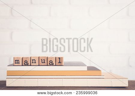 The Word Manual Guide, Text On Wooden Cubes On Top Of Books. Background Copy Space, Vintage Minimal