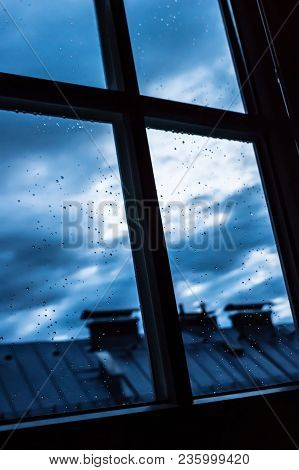 View Out Of A Window At A Rainy Day On A City Roof With Drops On The Glass