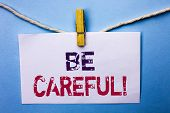 Text sign showing Be Careful. Conceptual photo Caution Warning Attention Notice Care Beware Safety Security written White Note Paper hanging with rope the plain background Clip. poster