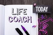 Handwriting text Life Coach. Concept meaning Mentoring Guiding Career Guidance Encourage Trainer Mentor written Notebook Book wooden background Today with Thumbpin Marker Paper Clip. poster