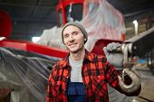 Young smiling man in workwear looking at camera during working day at modern shipbuilding factory poster