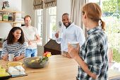 Four young adult friends having coffee in the kitchen poster