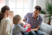Little son presenting gift for dad, cute boy holding box making daddy surprise present, kids congratulating excited happy parent with birthday, young family celebrating fathers day together concept poster