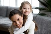 Happy single mother laughing piggybacking little girl at home, smiling mom and daughter having fun playing looking at camera, cute sincere adopted kid embracing new mommy head shot portrait poster