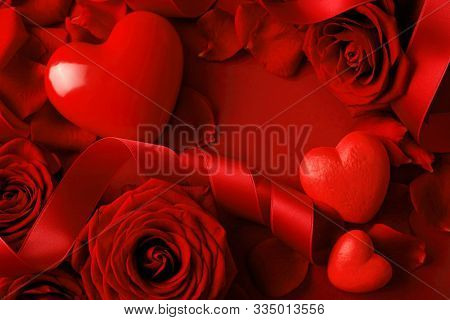 red hearts, ribbon and rose petals on red background. Valentine's Day decoration