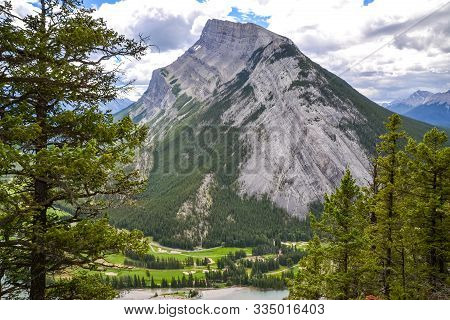 Peering Through The Pine Trees On A Mountain Hiking Trail, The Rocky Mount Rundle Stands Tall And Pr
