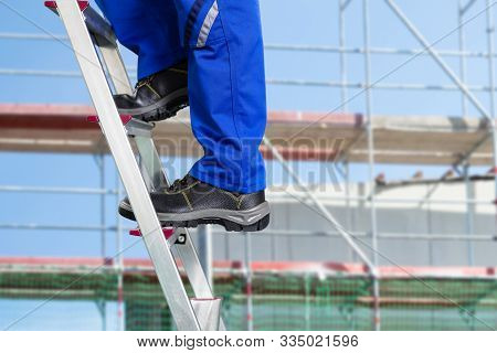 Close-up Of A Handy Repair Man Standing On Steel Ladder Against Construction Sites