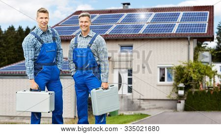 Portrait Of Smiling Electricians Holding Tool Boxes Standing In Front Of House With Solar Panel