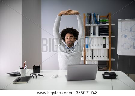 Young Businessman Stretching His Arms With Laptop On Desk