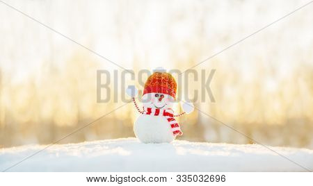 Snowman in winter wonderland scene. Christmas, New Year postcard design. Wintertime magic. Snowman in december snow at sunset
