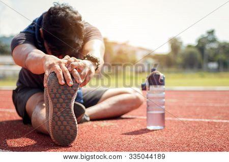 Runner Man Is Stretching Legs Preparing For Run Training On Track.