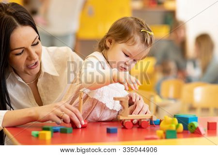 Little Caucasian Child Girl Playing With Montessori Toy In Pre-school. Woman Teaching Kid In Kinderg