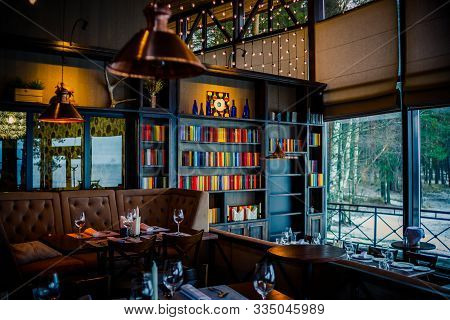 Russia, Moscow -13 February 2019. Wonderful Restaurant In A Loft Style. Brown Chairs, Shelves With D