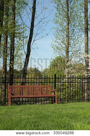Park Bench. A Wood Park Bench Near A Fence With Spring Trees Blooming In The Background