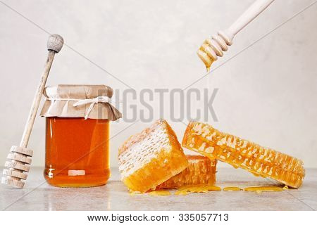 Honey Background. Sweet Honey In The Comb, Glass Jar And A Spoon For Honey On The Table. Light Backg