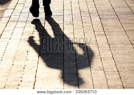 Silhouette And Shadow Of Man Walking The Street, Dramatic Colors. Concept Of Criminal, Murderer Or M