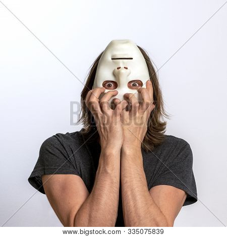 A Long-haired Man In A Gray T-shirt Covers His Face With A White Mask Upside Down And Tries To Tear