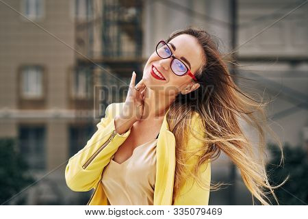 Portrait Of A Young Beautiful Laughing Woman With Long Hair Wearing Glasses And A Yellow Jacket On A