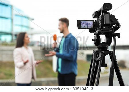 Young Journalist Interviewing Businesswoman On City Street, Focus On Camera Display