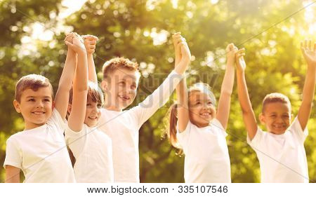 Group Of Children Holding Hands Up In Park On Sunny Day. Volunteering With Kids