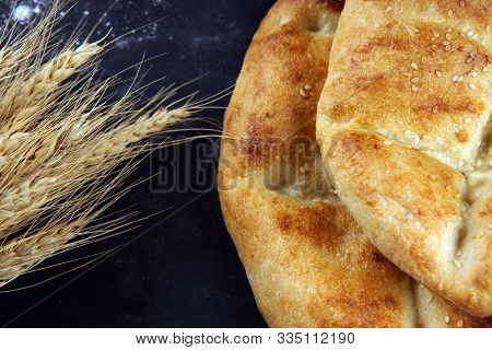 Two Pita Bread With A Golden Crust Lie On The Table Next To The Ears Of Wheat