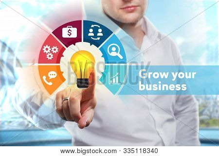 Business, Technology, Internet And Network Concept. Young Businessman Shows The Word: Grow Your Busi