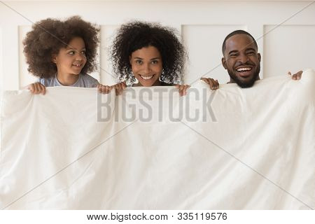 Smiling Biracial Family With Kid Peek From White Duvet