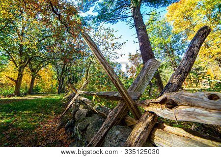 Autumn View Of Spiky Old Fencing Protecting Rock Wall Along Historic Battle Road In Concord, Ma, Usa