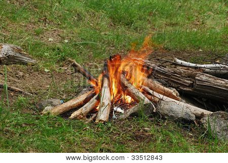 Red yellow camp fire at green glade poster