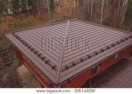 Modern Roof Made Of Metal. Corrugated Metal Roof And Metal Roofing. House With A Brown Metal Roof.