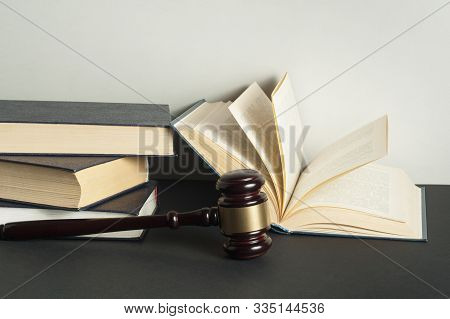 Law Concept - Books With Wooden Judges Gavel On Table In A Courtroom Or Enforcement Office.