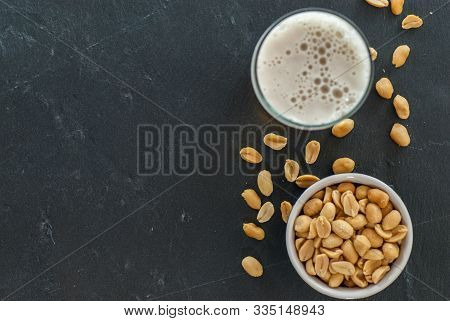Glass Of Beer And Bowl With Roasted And Salted Peanuts On Slate Social Drinking Concept