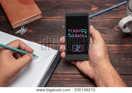 Cash Back Message On Hand Holding To Touch A Phone, Top View, Table Computer Coffee And Book
