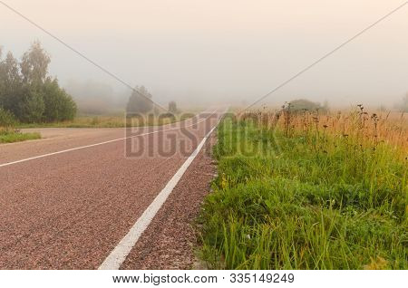 A Road To Fog. A Road In The Countryside Disappears Beneath Dense Fog.