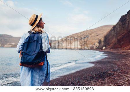 Tourist Walking On Red Beach By Aegean Sea In Akrotiri, Santorini Island, Greece. Woman With Backpac