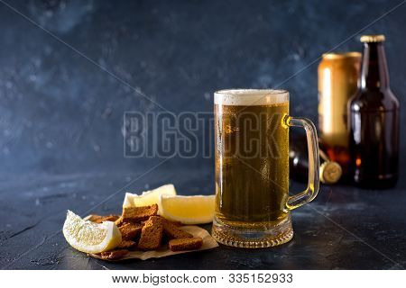 Glass Of Cold Beer And Botle Chips On Wooden Table