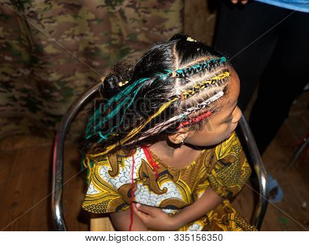 African Hairdresser Plaits Braids With Multicolored Artificial Strands For Mixed Jamaican European E